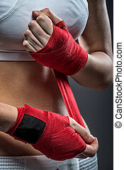 Boxing woman binds the bandage on his hand, before training, detail photo