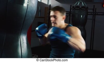 Boxing Workout:  training with a punching bag in a boxing club.