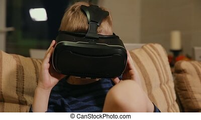 Boy 6-7 years playing at home with the help of virtual...