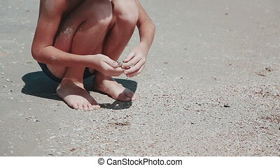 Boy 9 years old sitting on the sand of the sea by the sea. Playing sea sand, waves wash the feet of the child.