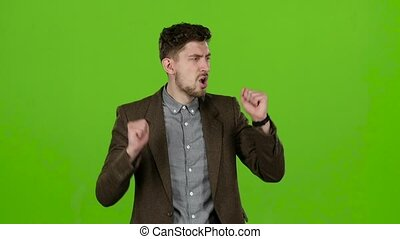Boy a businessman, rejoices at his victories. Green screen. Slow motion