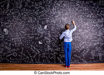Boy against big blackboard with mathematical symbols and...