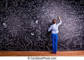 Boy against big blackboard with mathematical symbols and...