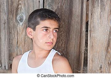 Boy against old barn wall