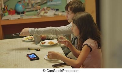 boy and a girl changes channels TV remote control watch, drink tea and eat cake