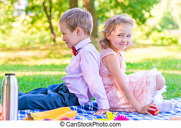 boy and a girl of 6 years on a picnic sitting back to back