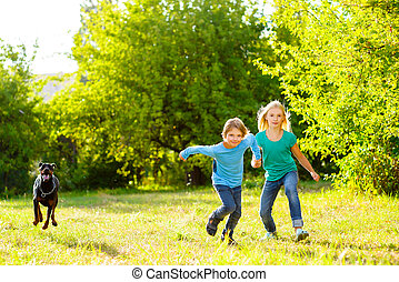 boy and a girl running away from dog or doberman in summer park