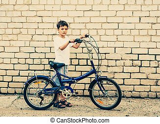 Boy and bicycle against brick  wall