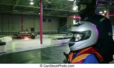 Boy and coach in racing helmets watch carting ride