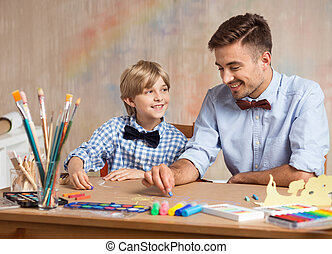 Boy and dad painting together at home