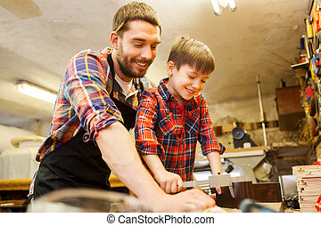 boy and dad with calipers measure wood at workshop - family,...