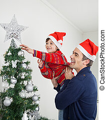 Boy And Father Decorating Christmas Tree