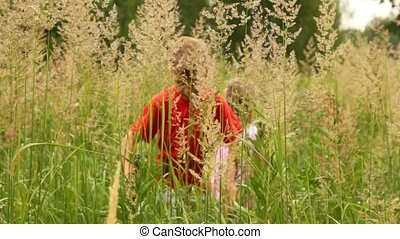 boy and girl are working way through thick grass - boy and a...