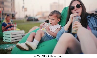 Boy and girl, brother and sister spending time at the park. Sitting in bag chairs, drinks water, dancing and laughing