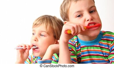 boy and girl brush teeth - boy and girl in striped sweaters...