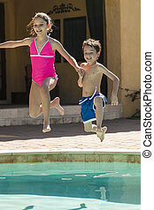 Boy and Girl Children Jumping into Swimming Pool