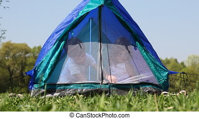 Boy and girl close zipper mosquito net sitting inside tent -...