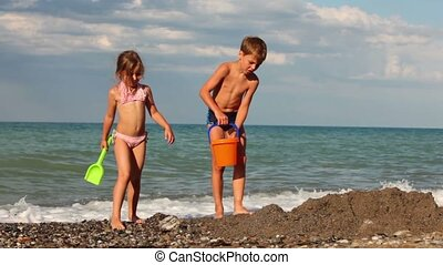 Boy and girl, coming to the pit in the sand