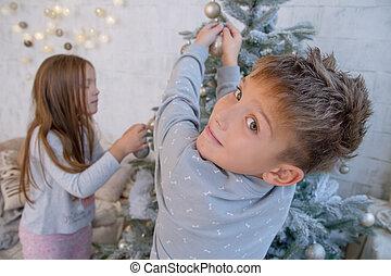 Boy and girl decorating Christmas tree