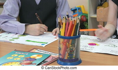 Boy and girl draw the pictures in the copybook - Little boy...