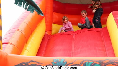 boy and girl drive off with big red inflatable rubber slides, then climb back to top