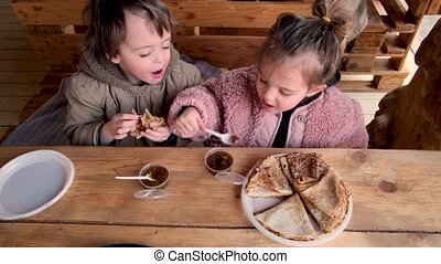 Adorable little boy and girl eat delicious fresh crepes with fruit jam sitting at rustic wooden table in comfortable cafe