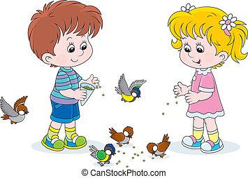 Boy and girl feeding birds - Little children feed a small...