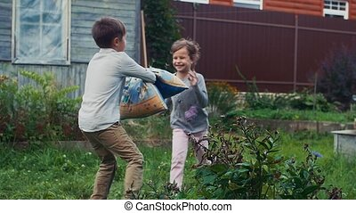 Boy and girl fight pillows in yard of country house....