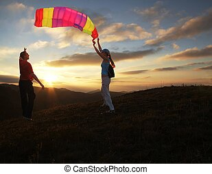 Boy and girl flying a kite on sunset