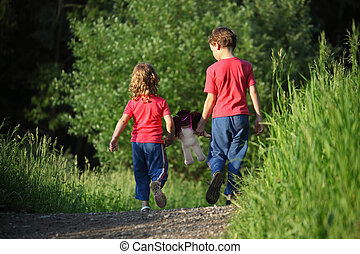 boy and girl go for a walk with doll in park, rear view
