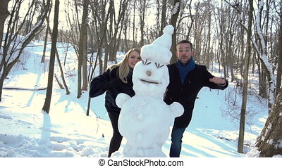 Boy and Girl Having Fun with Snowman