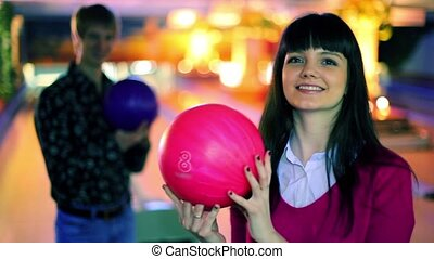 boy and girl hold bowling balls and smile, and then make...