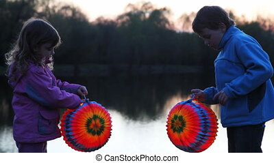 boy and  girl hold colorful ball from paper at night