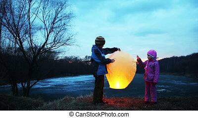 boy and girl holding, gently touch chinese lantern in winter woods