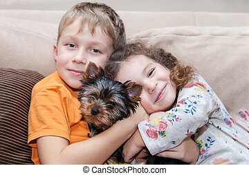 Boy and girl hugging puppy