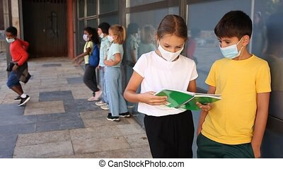 Portrait of primary school girl and boy wearing protective face masks talking outside before lesson, new normal during coronavirus pandemic situation