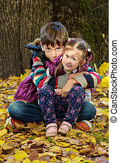 Boy and girl in sunny autumn park sitting on leaves