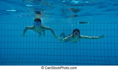 Boy and girl in swimming pool swim underwater