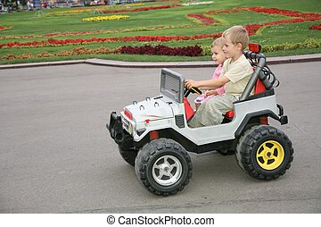 boy and girl in toy car