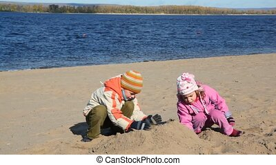 boy and girl is digging in sand of beach