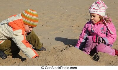 boy and girl is digging sand and constructing buildings -...