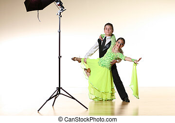 Boy and girl isolated over white wall posing for photoshoot in ballroom dance studio