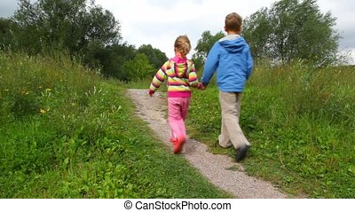 boy and girl join hands walking in park, from camera
