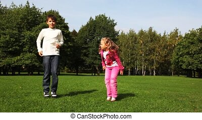 Boy and girl jumps on field before trees