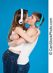 boy and girl kissing, wearing headphones in the studio
