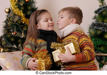 Boy and girl kissing with gifts over Christmas tree