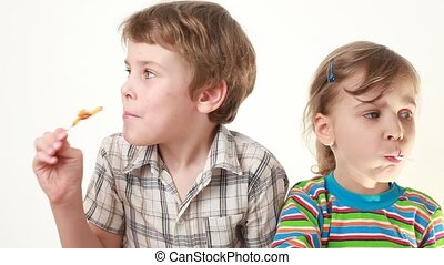 boy and girl licking and looking at lollipops in chicken form