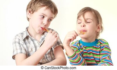 boy and girl licking lollipops in chicken form
