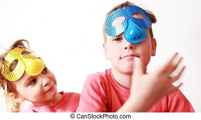 boy and girl lower masks on person, frighten each other and look in camera