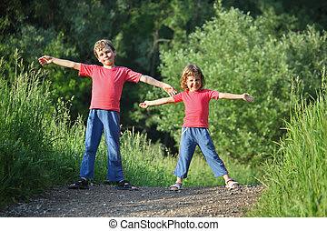 boy and girl make gymnastic in park